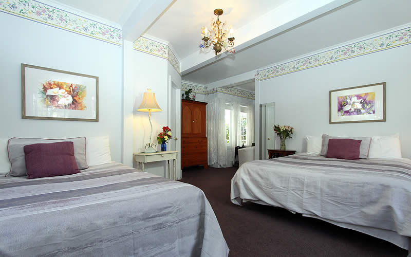 geranium room with two double beds and small sitting area