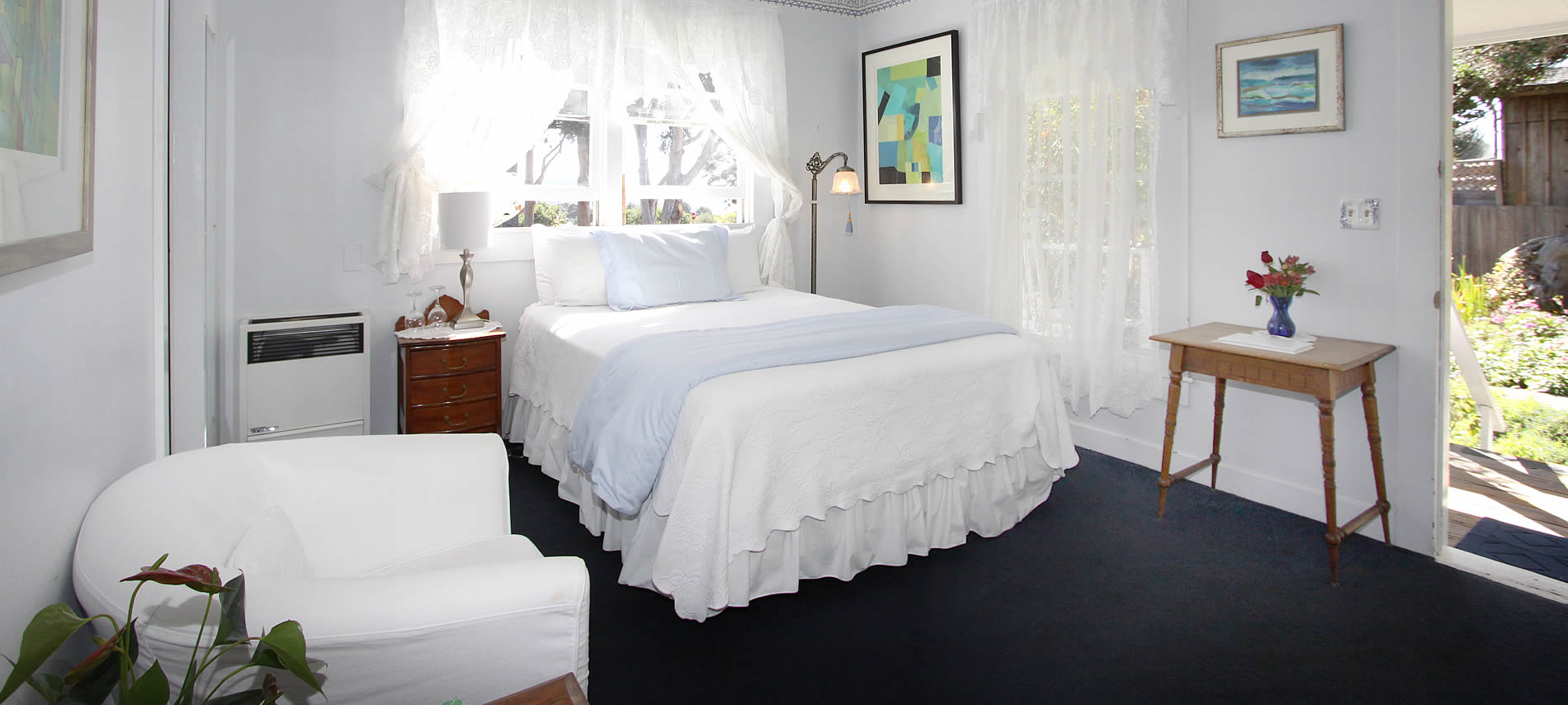 mendocino bed and breakfast guest room with white bed, blue carpet, sitting chair and table with flowers